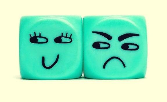 Würfel mit zwei verschiedenen Gesichtern: eines wütend, eines fröhlich