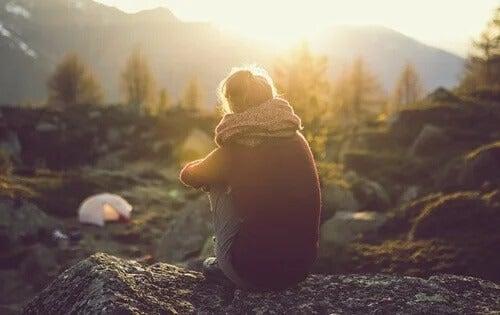 Frau sitzt allein über einem Campingplatz und schaut auf Wald und Berge