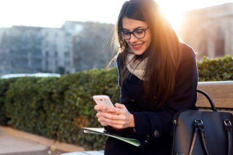 Frau auf einer Parkbank bedient ihr Handy