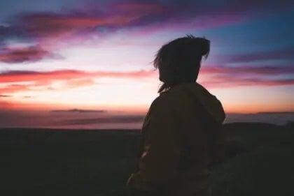Frau schaut sich Sonnenaufgang an