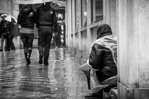 Eine Frau bettelt auf der Straße und mehrere Menschen gehen vorbei.
