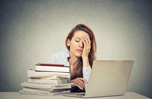 Eine Frau erschöpft an ihrem Arbeitsplatz