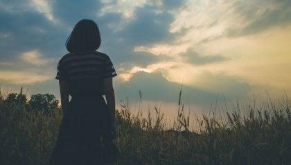 Eine Frau steht in einem Feld und beobachtet den Sonnenuntergang.