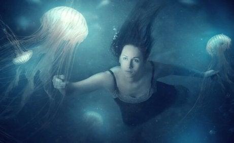 Frau schwimmt unter Wasser mit Quallen