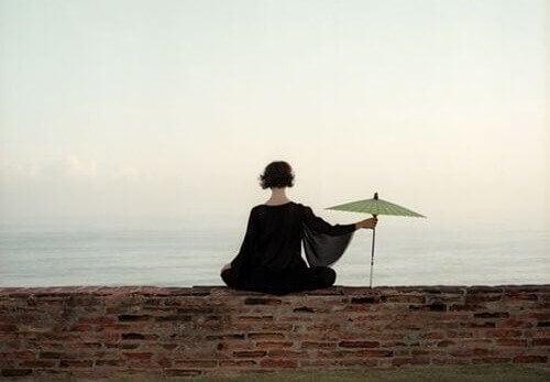 Eine Frau sitzt mit einem Regenschirm am Meer.