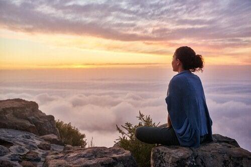 Eine Frau sitzt auf einem Berg über den Wolken.