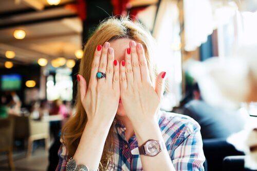 Eine junge Frau versteckt ihr Gesicht hinter ihren Händen.