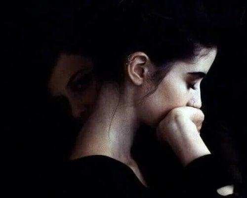 Frau mit zwei Gesichtern stützt sich auf ihre Hand