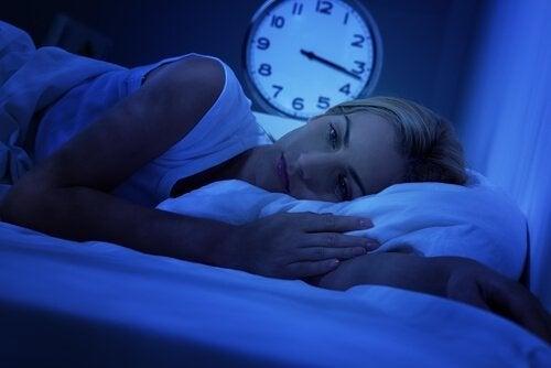 Frau im Bett wacht mitten in der Nacht auf