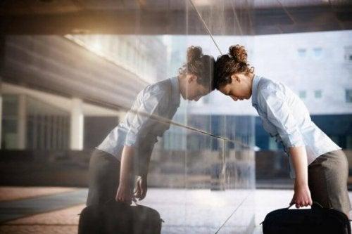 Eine frustrierte Frau steht mit ihrem Kopf an eine Wand gelehnt.