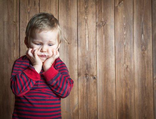 Ein frustriertes Kind greift sich ins Gesicht.