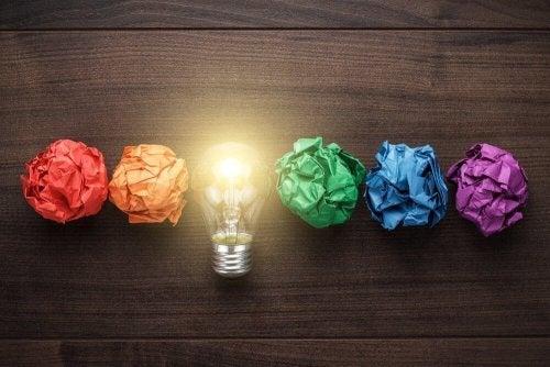 Eine Glühbirne und verschieden farbige Papiere liegen auf einem Tisch.
