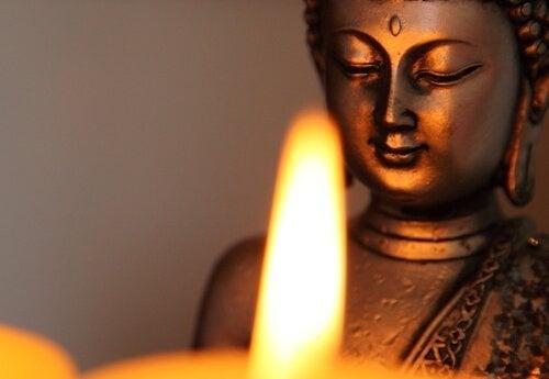 Eine Buddha-Statue vor einer Kerze