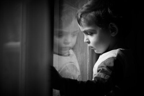 Ein kleiner Junge schaut traurig aus dem Fenster.