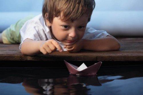 Kleiner Junge spielt mit einem gefalteten Papierschiff.