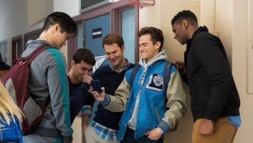 Jungen auf dem Schulhof lachen, während sie auf ein Handy schauen