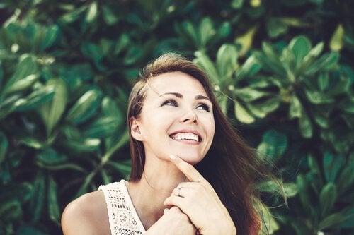 Eine lachende Frau denkt nach und wartet auf Inspiration.