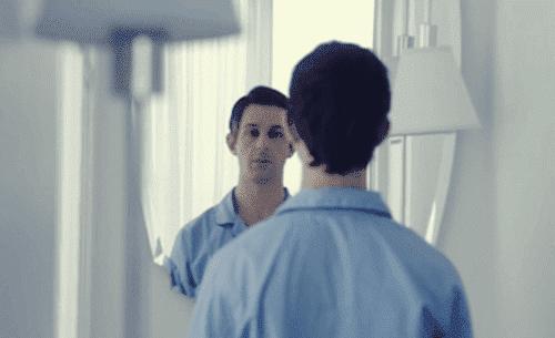 Ein Mann betrachtet sich im Spiegel.