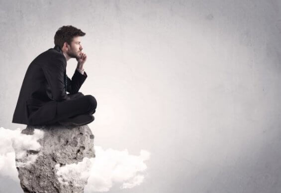 Denkender Mann sitzt auf einem Fels