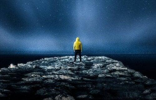 Ein Mann schaut in der Nacht in den Sternenhimmel.