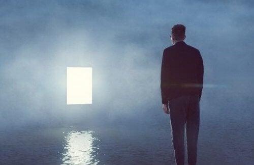 Mann, der eine offene Tür auf der anderen Seite des Wassers betrachtet