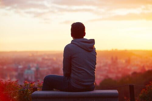 Ein introvertierte Mensch sitzt allein auf einem Dach und beobachtet den Sonnenuntergang.