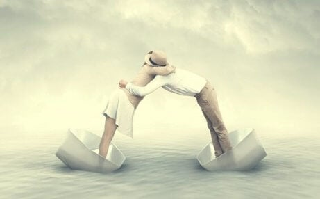 Mann und Frau umarmen sich, während sie in kleinen Papierbooten auf dem Meer schwimmen