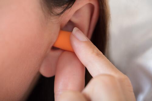 Eine Frau, die Ohrstöpsel zum Schlafen benutzt