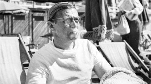 Jean-Paul Sartre sitzt in einem Strandkorb.
