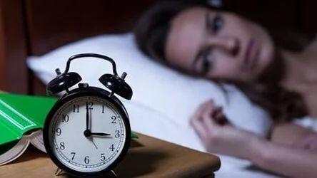 Frau liegt nachts wach im Bett