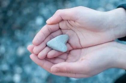 Hände, die ein kleines Herz aus Stein halten