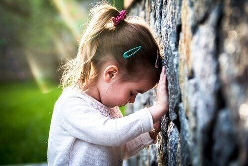 Ein trauriges Mädchen lehnt an einer Wand.