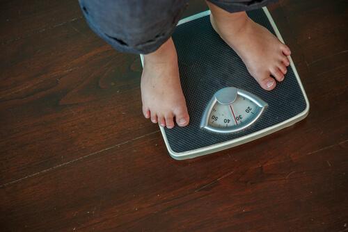 Übergewichtiger Mann, der sich wiegt