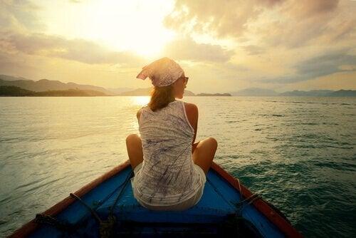 Ein Frau sitzt auf dem Bug eines Holzbootes.