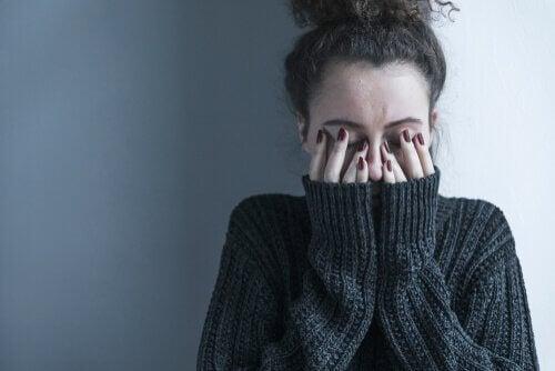 Depressive Frau, die sich die Augen zuhält