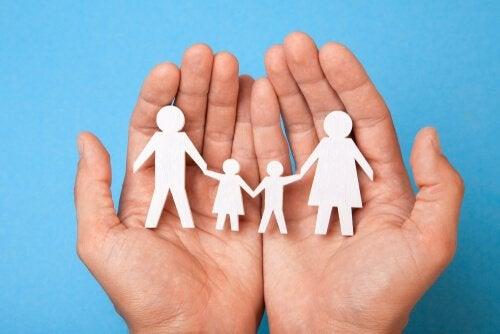 Familie als Scherenschnitt in offenen Händen