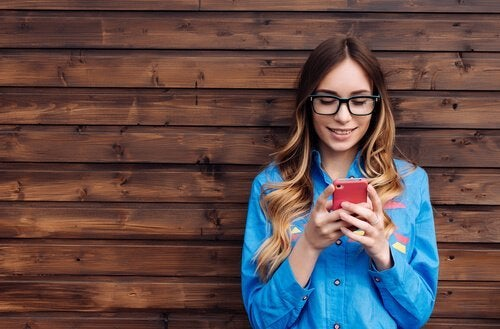 Junge Frau vor einer Wand schaut auf ihr Telefon