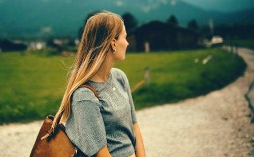 Frau auf einem Feldweg schaut über ihre Schulter zurück