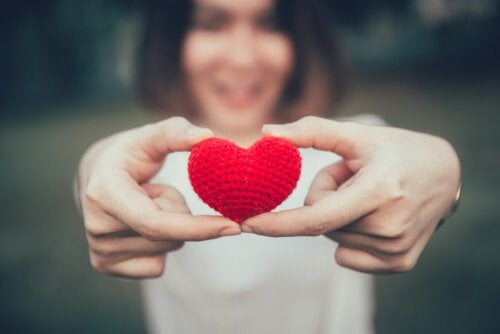 Frau, die ein Herz in den Händen hält
