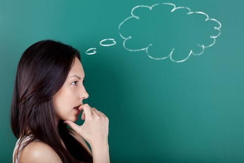 Eine Frau mit Gedankenblase über sich denkt nach.