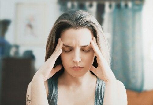 Frau im Stress fasst sich an die Schläfen