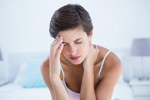 Frau mit Migräne fasst sich an den Kopf