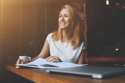 Frau sitzt lachend an einem Tisch