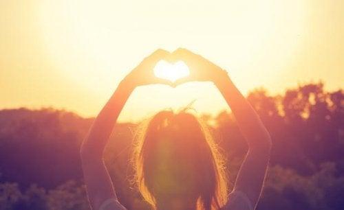 Hände formen ein Herz gegen die Sonne