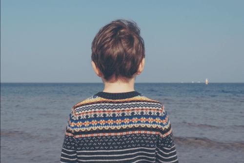 Ein trauerndes Kind, das den Ozean betrachtet