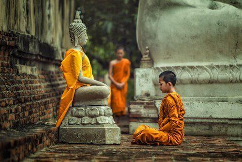 Junger Mönch sitzt vor einer Statue von Buddha
