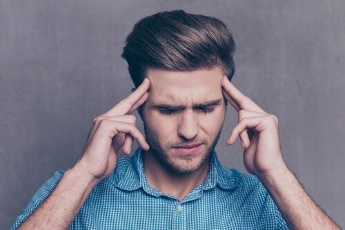 Ein Mann mit geschlossenen Augen und den Fingern an den Schläfen