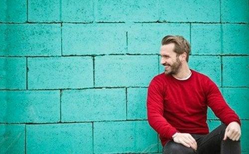Ein Mann mit einem roten Pulli lehnt an einer Wand.