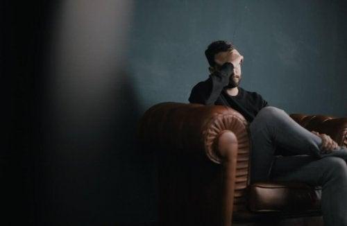 Mann sitzt auf einer Couch und stützt seinen Kopf auf seine Hand