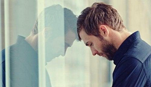 Mann stützt sich mit dem Kopf an einem Fensterglas